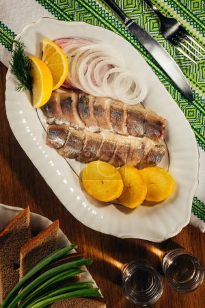 Top view of herring fish pieces with lemon and onion on white plate served with drink in glasses