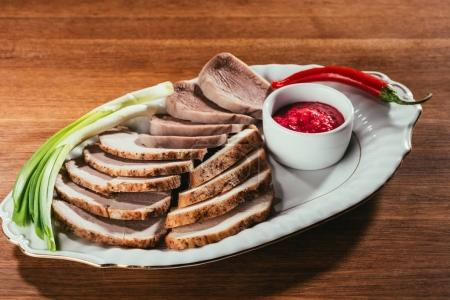 view of ham sliced on white plate with saucer and red peppers on table