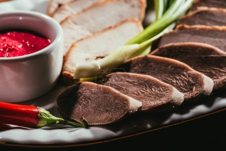Close-up view of assorted meat slices served with sauce, green onion and pepper on white plate
