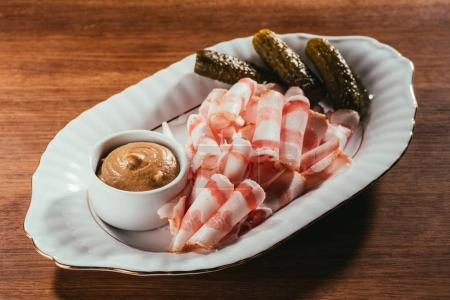 Photo for View of cold-boiled pork with mustard in saucer on white plate over wooden surface - Royalty Free Image