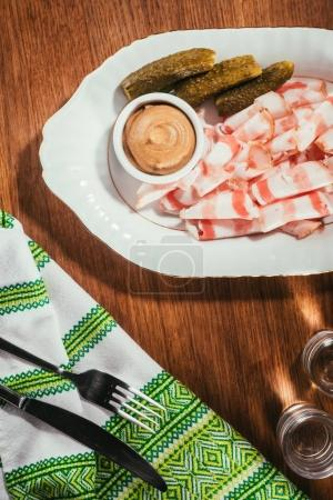 Top view of sliced bacon served with sauce and pickled cucumbers on plate served with drink on wooden table with napkin on wooden table