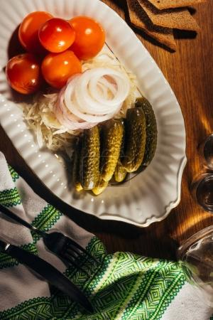 Top view of sauerkraut served with pickled vegetables on white plate on wooden table with napkin