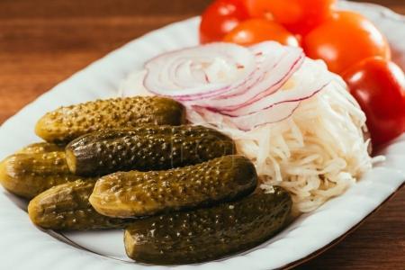 Photo pour Vue rapprochée de la choucroute servi avec des légumes marinés sur une plaque blanche - image libre de droit