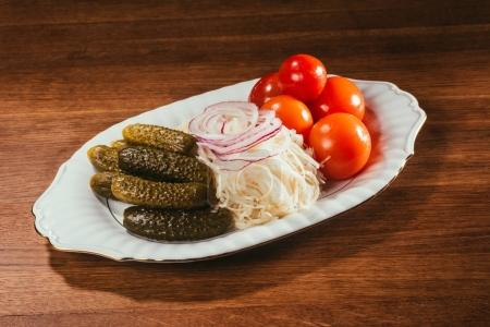 marinated salt cucmbers, sour cabbage with onion rings and raw tomatos laying on plate over wooden surface
