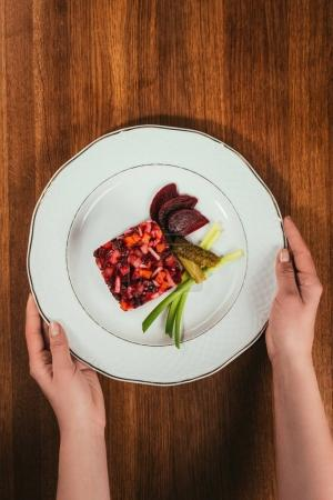 Top view of female hands holding plate with Vinegret salad served with green onion and pickled cucumber on wooden table