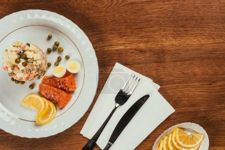 Top view of russian salad served with salmon and lemon on white plate on wooden table