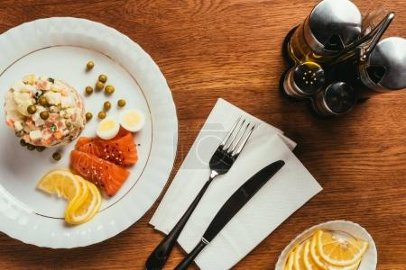 Russian salad on plate with scattered peas, boiled eggs and fish slices  over table with fork and knife on napkin