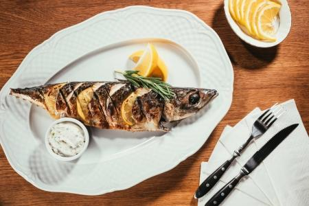 Baked fish with lemon and herbs on white plate with sauce on wooden table