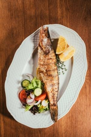 Top view of baked fish with lemon and herbs on white plate with salad on wooden table
