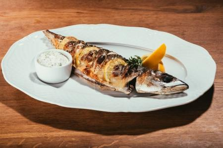 Photo for Fried fish laying on white plate with orange slices and sauce over wooden surface - Royalty Free Image