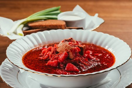 Photo for View of borsch soup with potato and meat in plate and green onions with bread and salt on background - Royalty Free Image