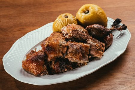 fried duck pieces laying on plate with marinated apples over wooden table
