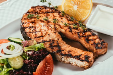 Photo for Close-up view of grilled salmon fish pieces with lemon, herbs and salad on white plate - Royalty Free Image