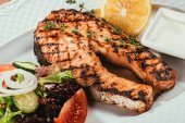 Close-up view of grilled salmon fish pieces with lemon, herbs and salad on white plate