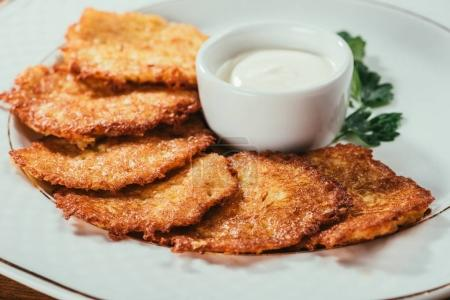 Photo for Close-up view of potato pancakes served with sour-cream sauce on plate - Royalty Free Image