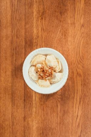 dumplings with fried onions on top laying in plate over wooden surface
