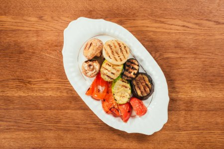 Top view of grilled vegetables and mushrooms on white plate on wooden table