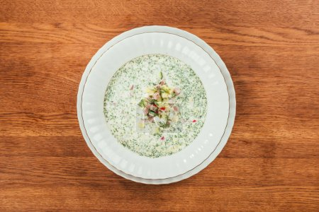 okroshka soup with herbs in white plate over wooden surface