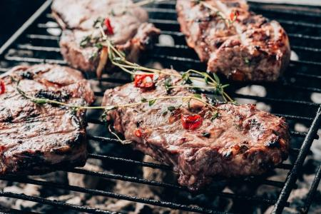 close-up view of delicious juicy meat with spices preparing on grill