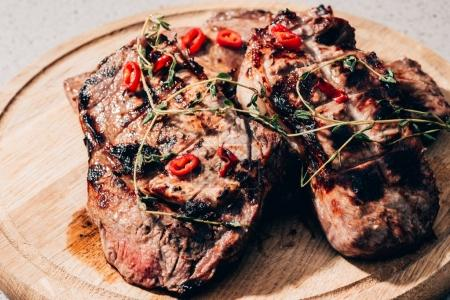 close-up view of delicious juicy grilled meat with spices on wooden board