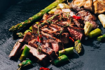 close-up view of gourmet sliced grilled meat with asparagus and spices on black