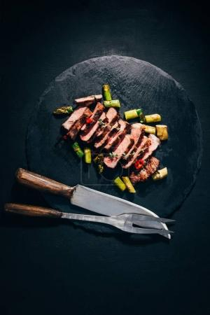 top view of delicious sliced grilled meat with asparagus, meat fork and knife on black slate board