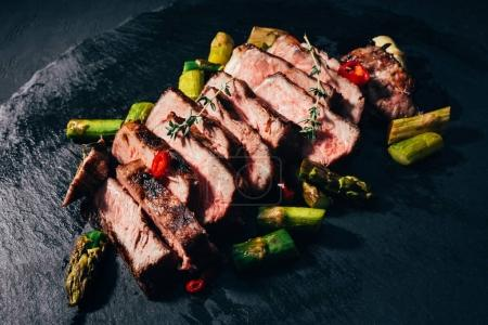 Photo for Close-up view of delicious sliced grilled meat with asparagus and spices on black slate board - Royalty Free Image