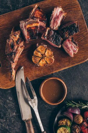 Photo for Top view of delicious grilled meat with fork, knife, sauce and vegetables on black - Royalty Free Image