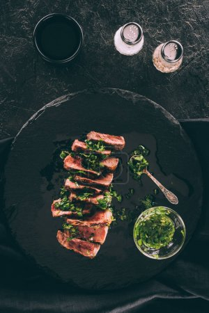 Photo for Top view of delicious sliced grilled meat with sauce and spices on black - Royalty Free Image