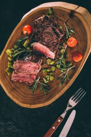 top view of gourmet grilled meat served with vegetables on wooden board