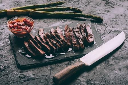 Photo for Close-up view of delicious sliced grilled meat with sauce and knife on black slate board - Royalty Free Image