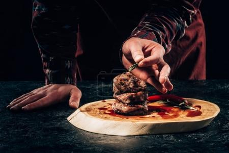 Photo for Close-up partial view of chef putting rosemary on grilled steaks with chili pepper and sauce on wooden board - Royalty Free Image