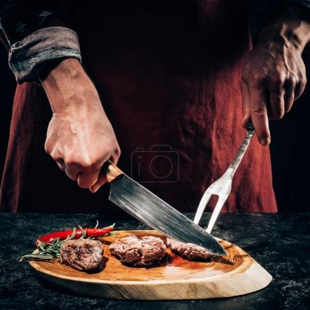 Photo for Close-up partial view chef in apron with meat fork and knife slicing gourmet grilled steaks with rosemary and chili pepper on wooden board - Royalty Free Image