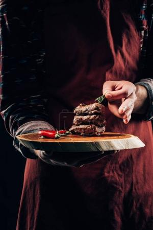 cropped shot of chef in apron holding wooden board with delicious grilled meat, chili pepper and rosemary