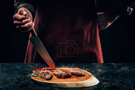 Photo for Cropped shot of chef in apron standing with knife and delicious grilled steaks with rosemary and chili pepper on wooden board - Royalty Free Image