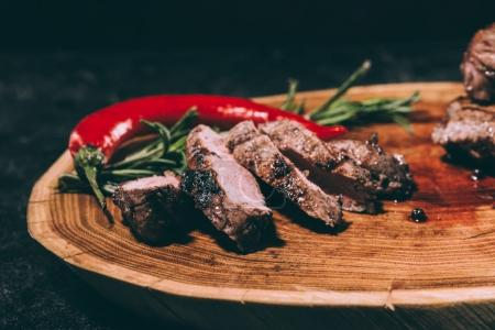 close-up view of delicious sliced grilled meat with rosemary and chili pepper on wooden board