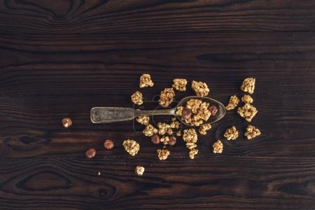 top view of crunchy granola and hazelnuts on spoon on wooden table