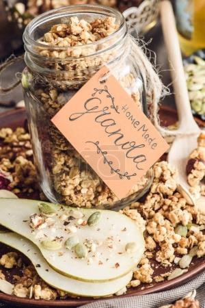 homemade granola in glass jar with tag on tray