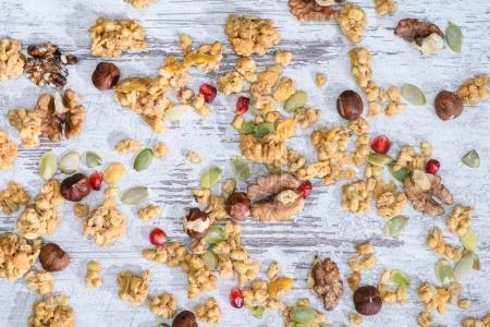 top view of scattered granola with nuts on grungy tabletop