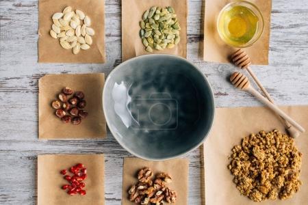 Photo pour Vue de dessus des ingrédients granola sur morceaux de parchemin et le bol sur la table de cuisson - image libre de droit