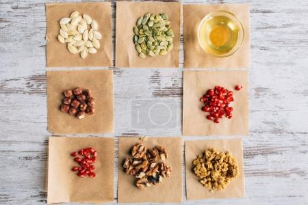 Photo for Top view of granola ingredients on baking parchment pieces - Royalty Free Image