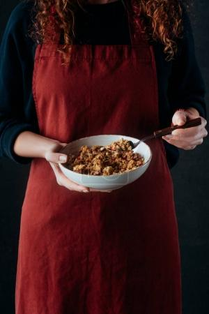cropped image of female cook holding bowl with granola and spoon