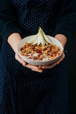 Photo for Cropped image of female cook holding bowl with homemade granola - Royalty Free Image