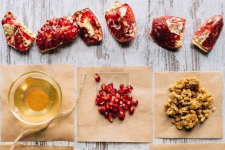 Foto de Vista superior de granadas y miel para la preparación de granola en la tabla - Imagen libre de derechos