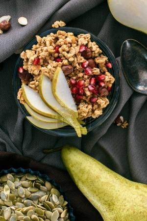 top view of crunchy granola with pears and pomegranate seeds on table