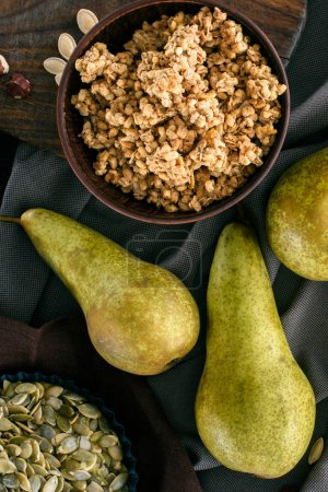 top view of crunchy granola and pears on table