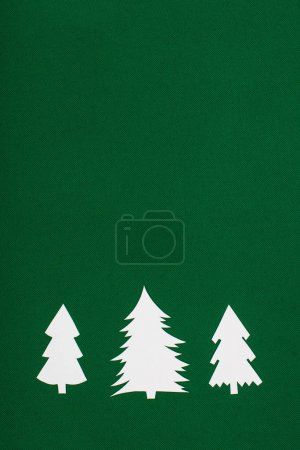 top view of decorative paper christmas trees on green background with copy space