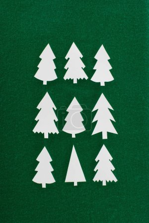 top view of decorative paper christmas trees on green background