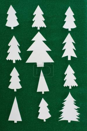 top view of white paper christmas trees on green background