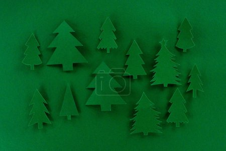 top view of green decorative paper christmas trees on green background